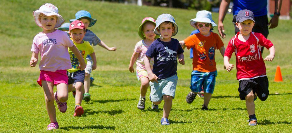 kids running on field in preschool sports program