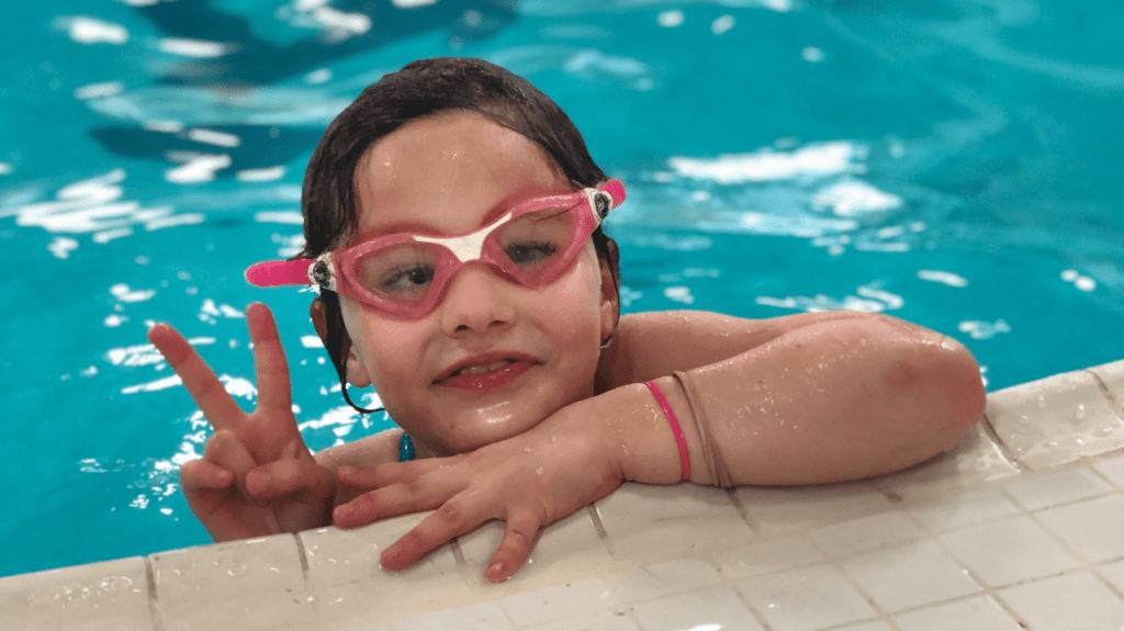 girl in swim lessons giving the peace sign