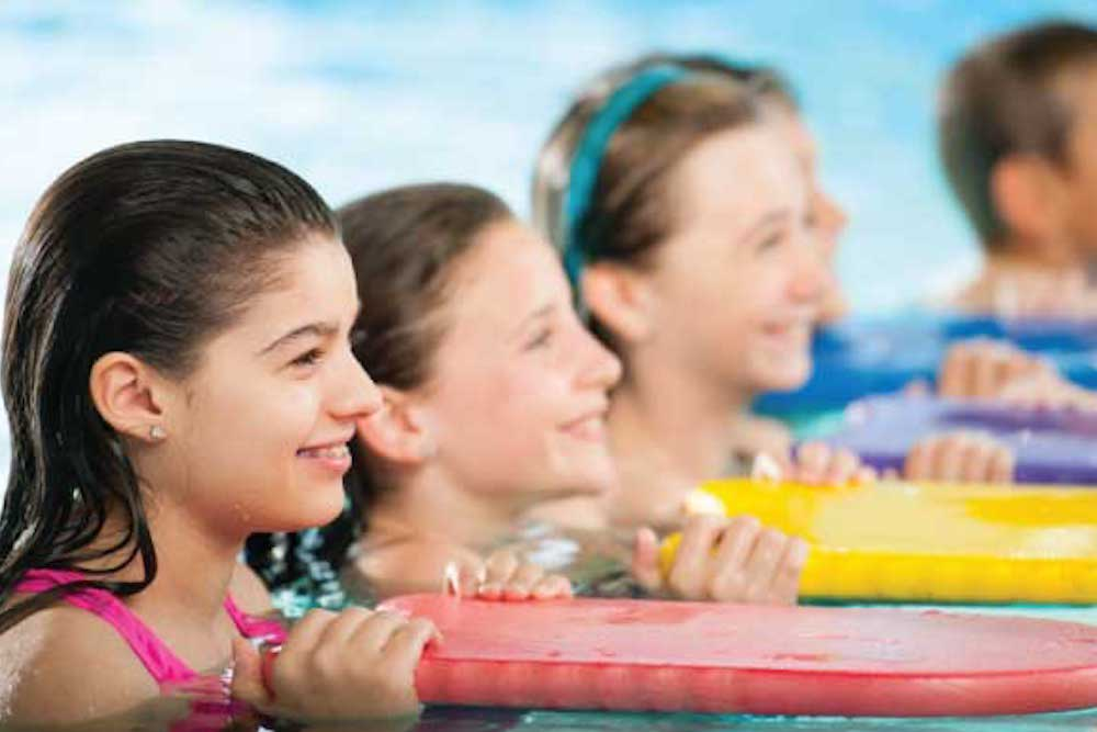 kids in swim lessons with flutter boards