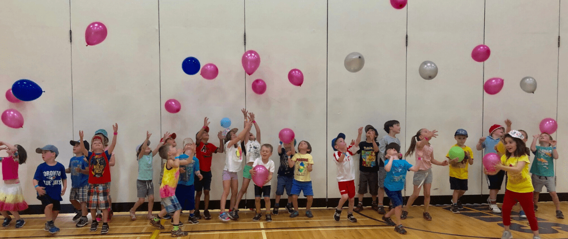 children throwing balloons in fun day camp