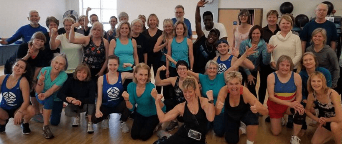 people smiling in a group fitness class