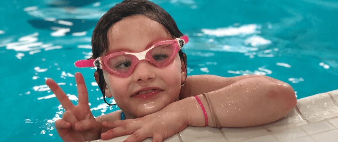smiling girl wearing googles swimming in pool