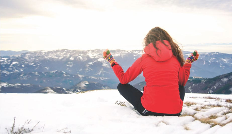Woman sitting in a yoga pose on a wintery hilltop