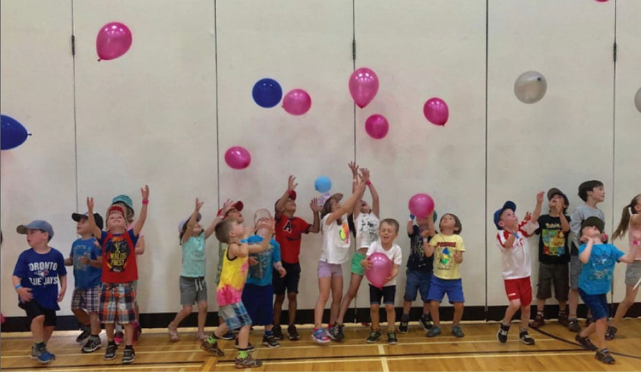 kids in the gym throwing balloons