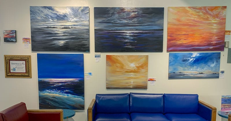 landscape acrylic paintings hanging on wall