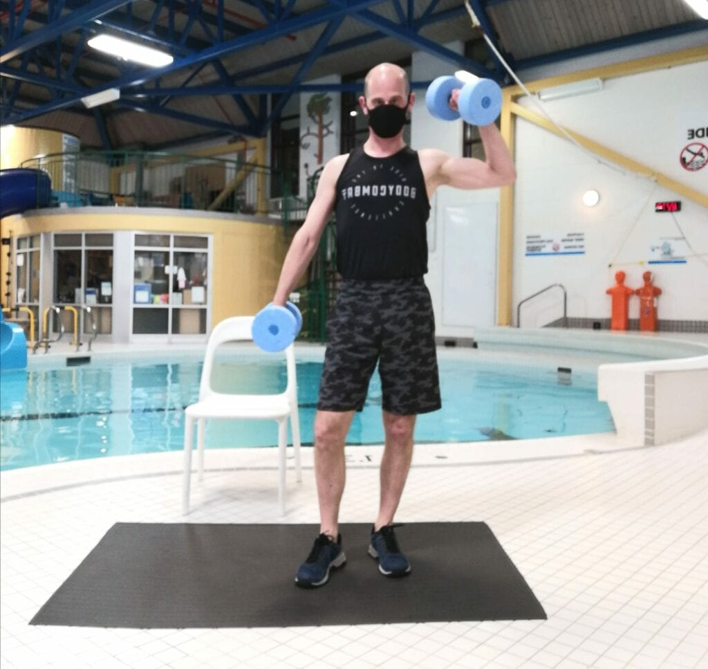 instructor stands on the pool deck for aquafit